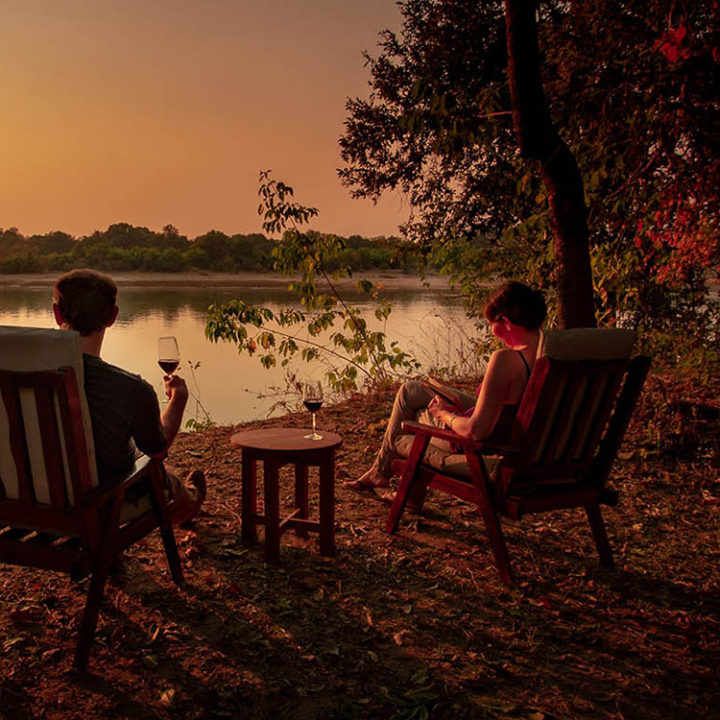 luambe-camp-lodge-zambia-in-style-tours-safari-packages-lodges-luambe-national-park-between-south-north-luangwa-river-bank-sundwoners-drinks-couple